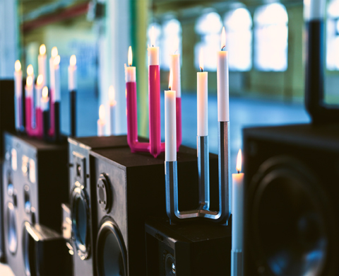 Candlesticks in silver-color, cerise, dark blue and white, on top of large loudspeakers. Each candlestick has three lit candles.