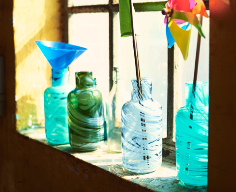 Four mouth-blown glass vases on a windowsill, all four are made of melted glass in various marble shades from leftover glass remnants.