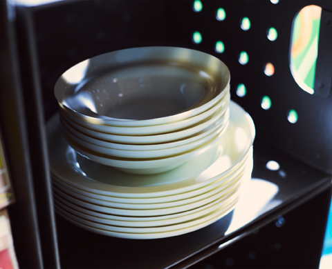 A stack of white tempered glass plates and bowls shown inside a black box.