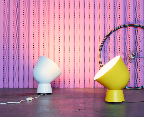 Two table lamps, inspired by old military searchlights, one white and one yellow.