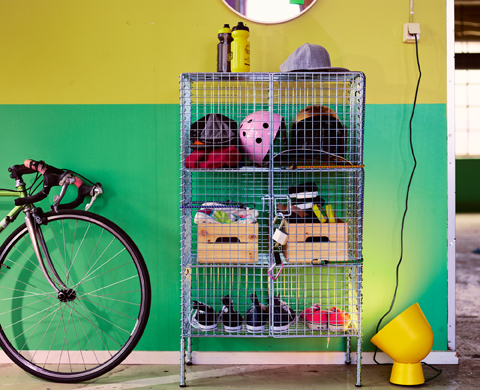 A steel cabinet in a cage design, with three shelves, two adjustable. Filled with shoes, bicycle helmets and wooden crates.