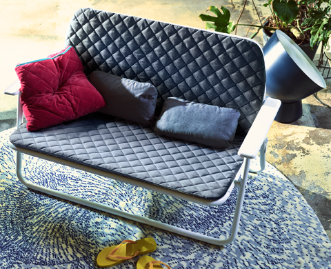 A small foldable two-seat sofa with grey quilted seat and back cushions, shown together with two grey cushions for lumbar support and an extra red cushion.