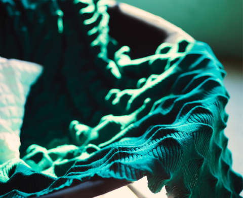 Close-up of a green knitted throw with a three-dimensional structure.