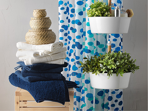 A tower of blue and white hand towels and differently sized seagrass boxes beside a blue and white spotted shower curtain and hanging planter.
