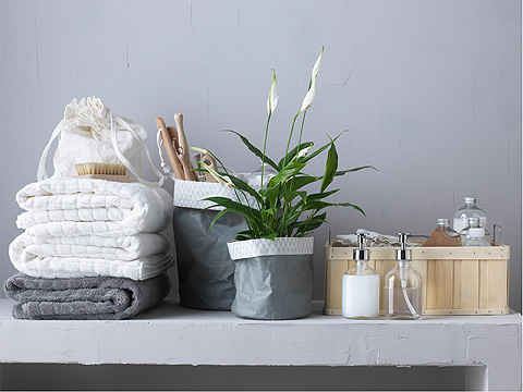 A pile of white and gray hand towels beside two plant pots and detergent dispensers and a basket.