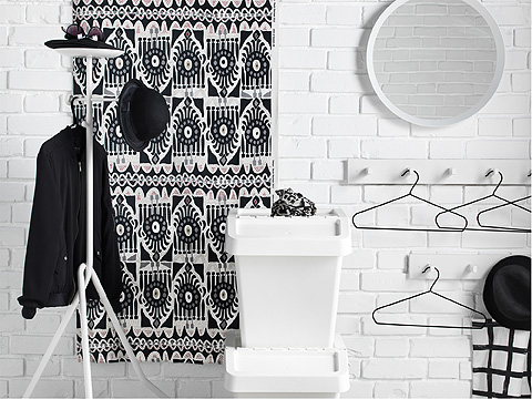 Freestanding and wall mounted clothes storage in a black and white hallway.