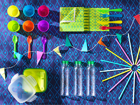 Colorful plastic cups, cutlery, straws and bottles on a blue patterned table cloth.