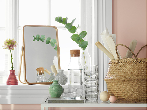 A table mirror and pink vase on a window sill beside a table with glasses, vases, a carafe and seagrass storage basket.