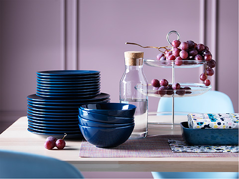 A stack of blue plates and bowls beside a glass carafe and tiered  cake stand on a wooden table.
