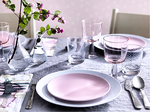 A pink and grey dinner setting with light pink plates and glasses.
