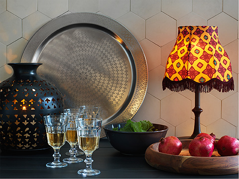 Sideboard with stainless steel serving dish, wine glasses, wooden fruit bowl and solarpowered lamp with patterned shade.
