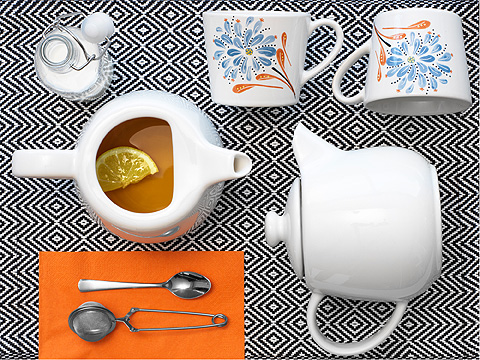 Two tea pots on a black and white place mat, with orange napkin and two flower-patterned teacups.