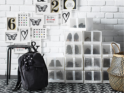 Stacked white shoe boxes and backpack in a black and white hallway with gallery wall.