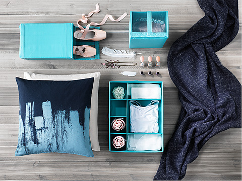 Light blue clothes storage boxes with dividers and a meshed window.