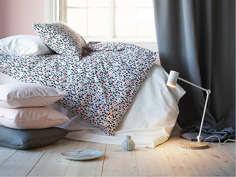 A pile of light pink and white cushions and floor lamp beside a bed with pink, blue and white quilt cover and pillow.