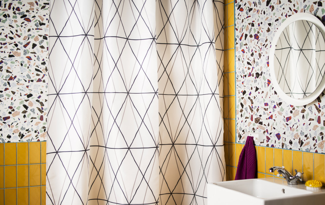 A bathroom with walls in yellow  and mosaic and a white shower curtain with black lined diamond pattern.