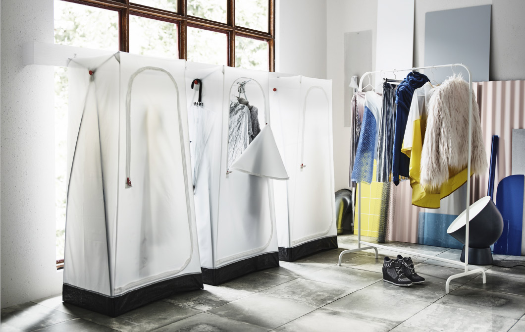A room with three portable textile wardrobes on a row, inspired by tents. Shown together with a white clothes rack with a fur jacket, a skirt and sweaters.