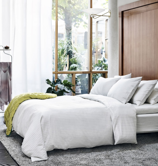 A large bed with six cushions and a quilt cover in white, made with a mix of cotton and lyocell with a beautiful lustre.