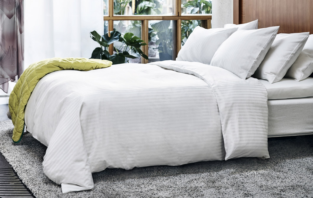 A large bed with six cushions and a quilt cover in white, made with a mix of cotton and lyocell with a beautiful luster.