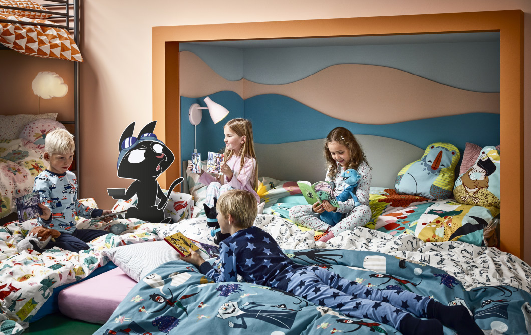 Four children having a sleepover on mattresses laying on the floor with quilt covers and pillowcases featuring fun and scary characters, such as vampires, ghosts, animals, letters and numbers.