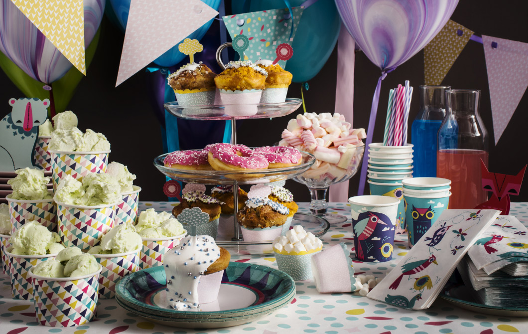 A table filled with ice cream cups with ice cream, a three-tier serving stand filled with decorated cup cakes, paper plates, cups and napkins with fun patterns and a glass bowl with candy.