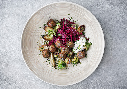 Vegetable balls with Brussels sprouts and pickled red cabbage served on a wooden plate, seen from above.