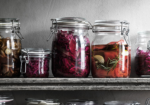 Glass jars on a shelf filled with pickled cabbage and red peppers.