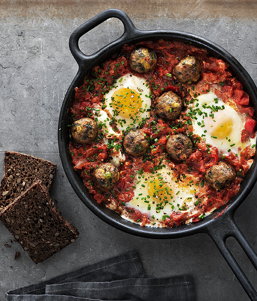Veggie balls in tomato sauce with poached eggs served in a cast iron frying pan, seen from above.