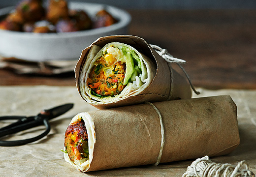 Veggie ball wrap with avocado served in parchment paper hold together with a string.
