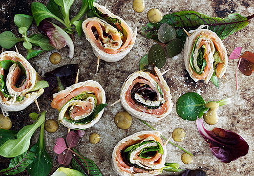 Mini wrap rolls with marinated salmon and mustard sauce served on a marble tray decorated with salad leaves and picked herbs, seen from above.