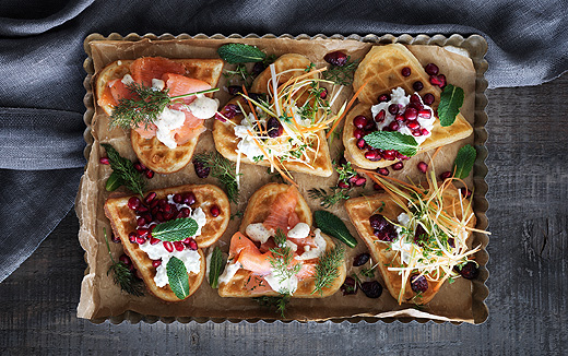 Waffles with various toppings, such as marinated salmon, dried cranberries with a mix of cress, leek and carrots and pomegranate seeds mixed with cottage cheese