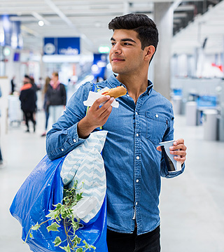 A man in a blue shirt holding a sausage in a bread in one hand and a beverage in the other, after shopping at IKEA.
