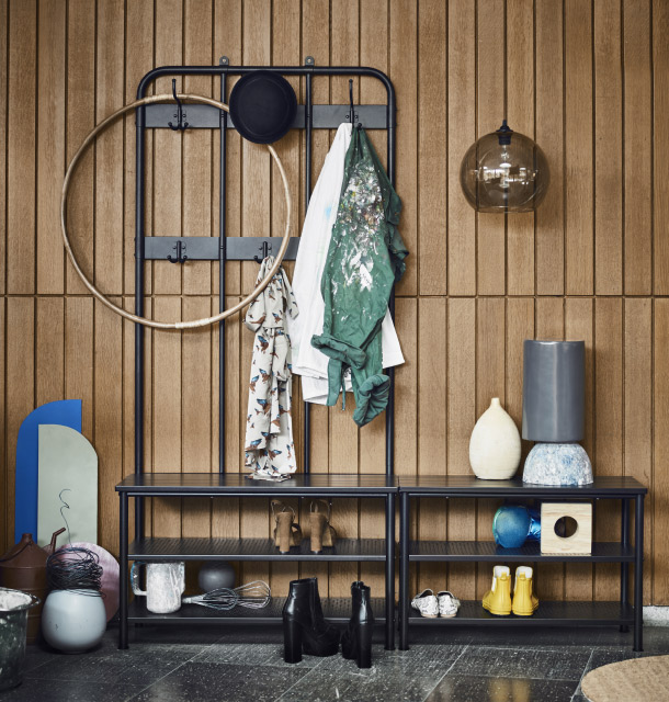 A hallway with a black steel coat rack with hooks and a storage bench filled with shoes, shirts, a hat and a hula hoop in bamboo.