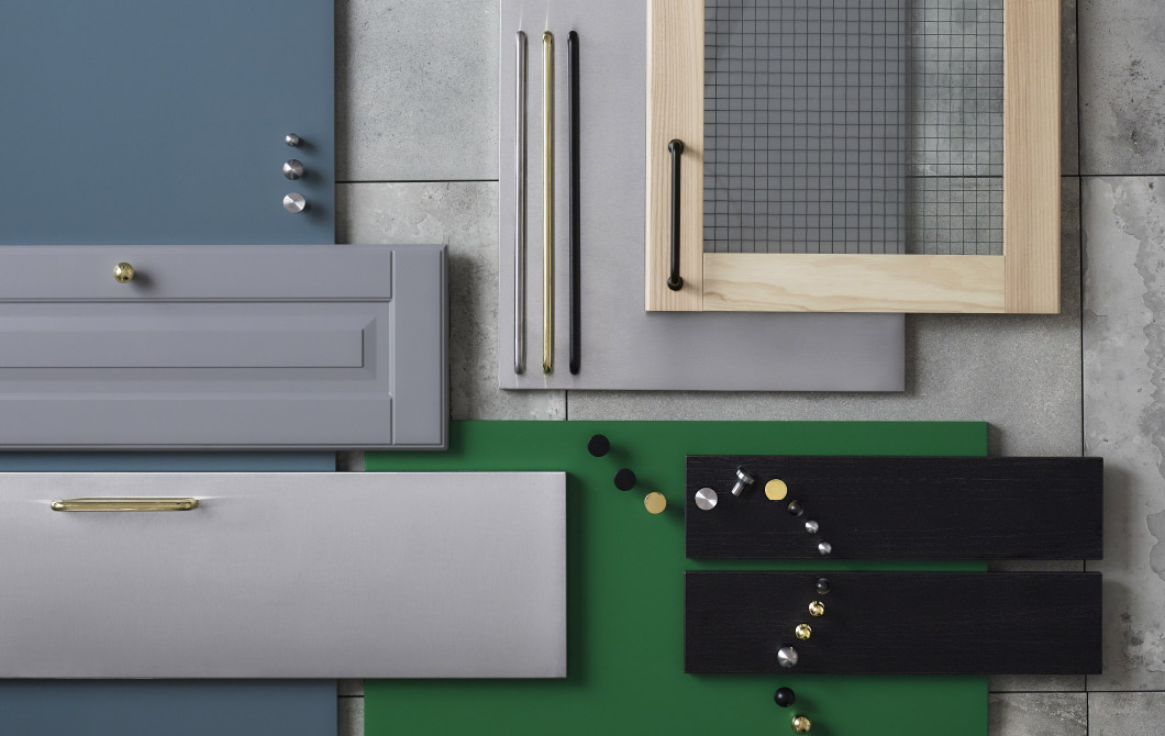 Display of kitchen doors and drawer fronts in various colours and materials. Shown together with handles and knobs in stainless steel, black and brass-colour.