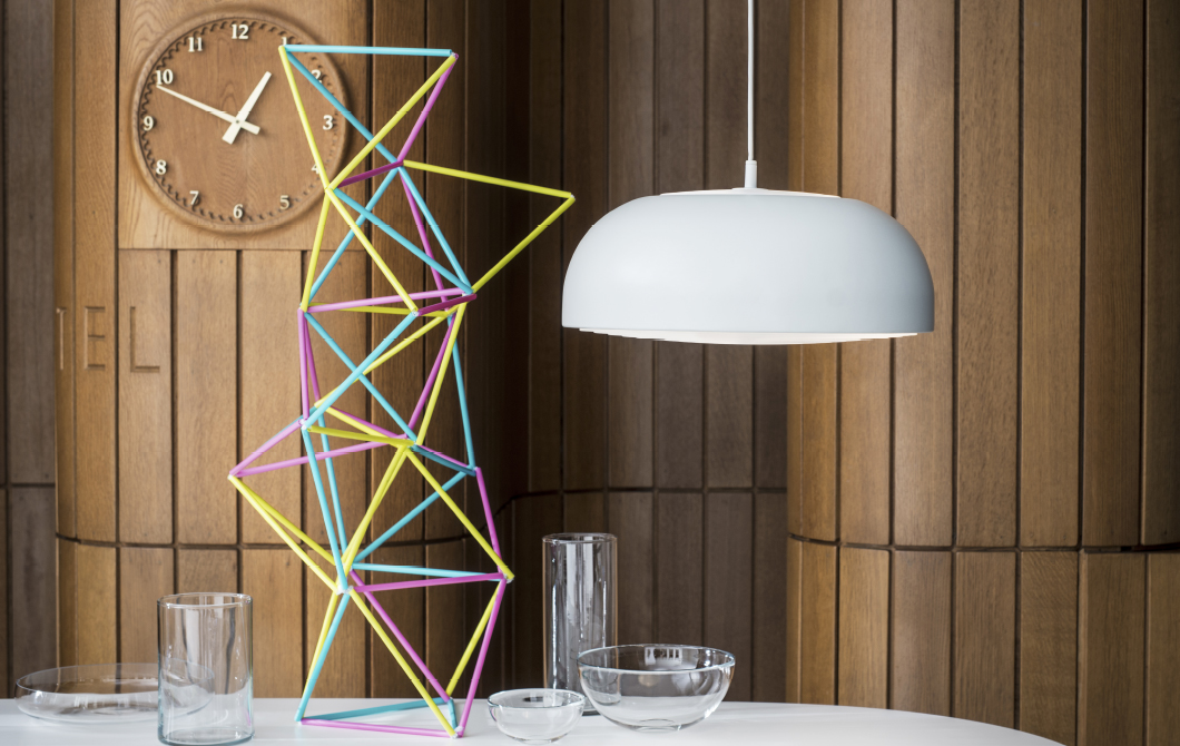 A white round pendant lamp hanging above a table with glass bowls, glasses and a tower made of yellow, pink and turquoise straws.