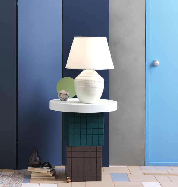 A white lit table lamp with a fabric shade and a stoneware base with embossed pattern, displayed on a round table.