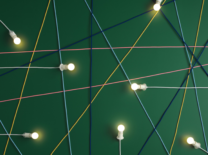 Several lit LED bulbs and a spider web made of cords in light blue, yellow, pink and dark blue, on a green background.
