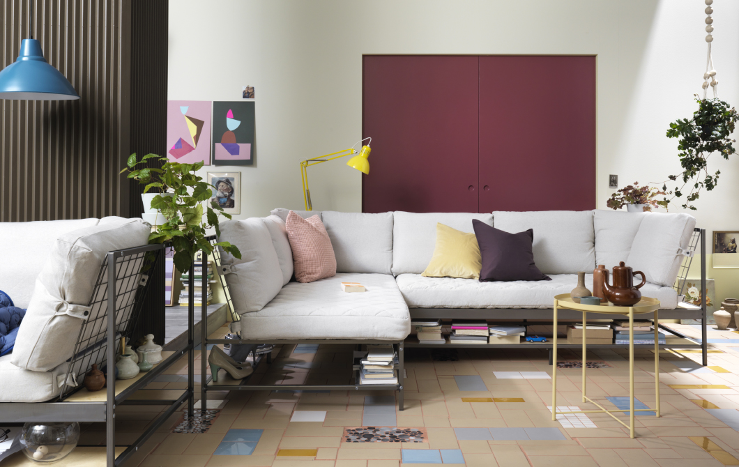 A living room with two three-seat sofas in grey steel mesh with natural-coloured cushions, put together as a corner sofa. Each sofa has a storage shelf underneath the seat with shoes and books.