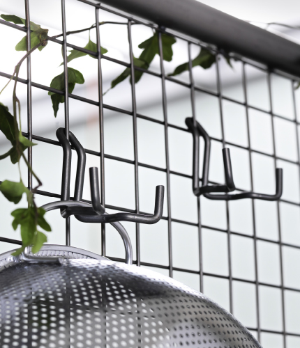 Close-up of a room divider with grey steel hooks.