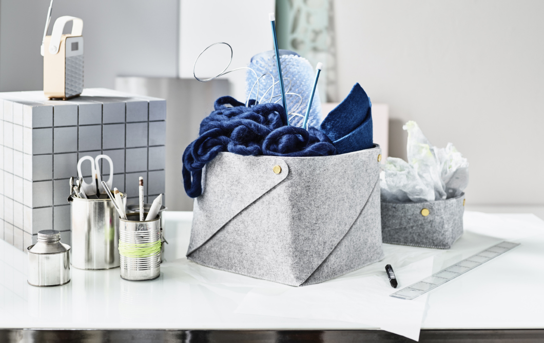 A white desk with a grey felt basketwith blue wool yarn and knitting needlesinside. Shown together with a smallerfelt basket with paper napkins.