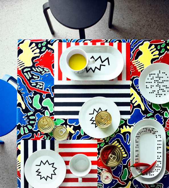 A table, seen from above, set with white plates and mugs featuring zigzag and irregular dot patterns. Shown together with striped place mats in black/white/red and a tablecloth with bright colors and funny patterns.
