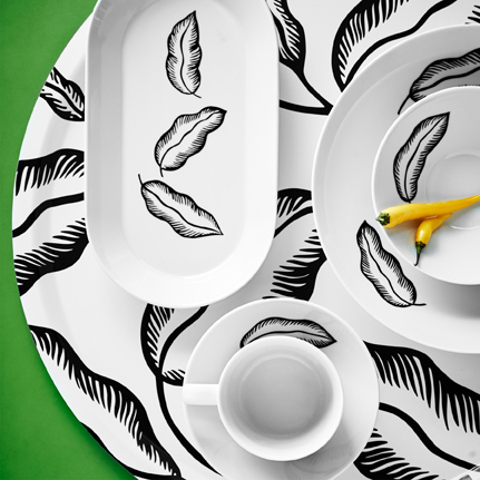 Close-up of a round white tray with black leaf pattern, seen from above, shown together with white plates and mugs also with black leaf pattern.