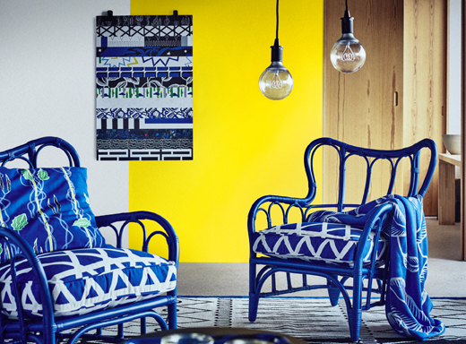 A living room featuring two blue handmade rattan armchairs with thick seat cushions in blue/white. On the wall behind the armchairs hangs a poster with stripes of many different patterns in blue, black, green and white