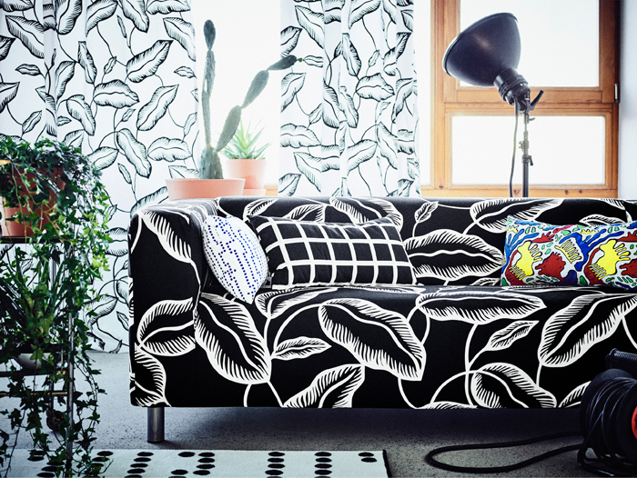 A living room with a two-seat sofa covered in a black fabric with white leaf pattern. Shown together with rectangular cushions in various colours and patterns.