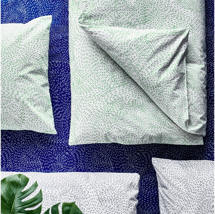 Close-up of pillowcases and quilt covers featuring organic shaped pattern in light green and blue, seen from above.