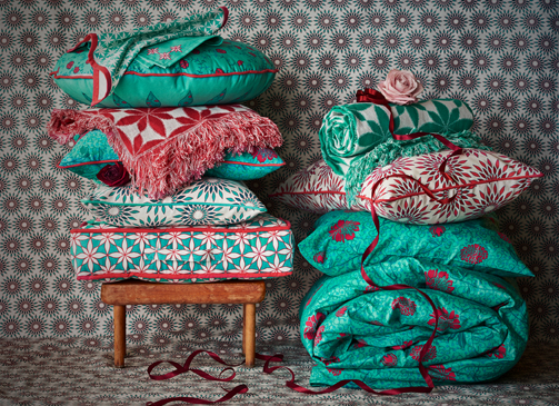 Two piles of textiles with floral or geometric patterns in turquoise, red and white. One pile with floor cushions, cushions, throws and place mats and the other with quilt covers and pillowcases.