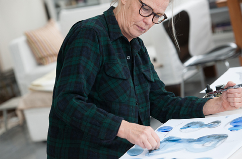 Gunnel Sahlin, designer at IKEA, standing by the drawing table and colouring a new design for the glassware line of the STOCKHOLM 2017 collection.