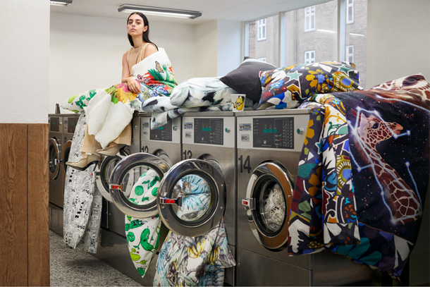 A woman sitting on a washing machine surrounded by quilt covers and pillowcases in various patterns.