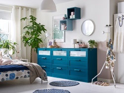 A bedroom in neutrals with three blue chest of drawers in a row.