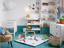 Blue and white nursery with white cot, changing table and chest-of-drawers.